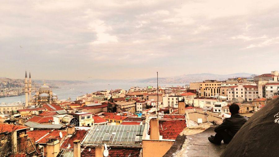 Cityscape and bosphorus against cloudy sky