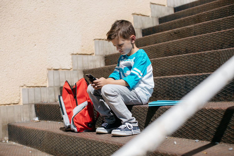 Full length of boy using on mobile phone while sitting on steps