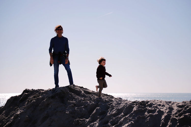 Father And Son On Rock Formation At Beach Against Clear Sky