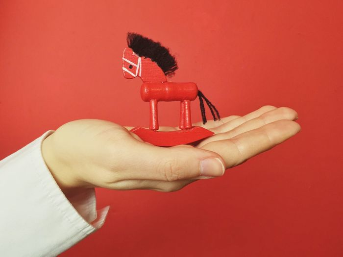 Cropped Image Of Woman With Wooden Toy Horse Against Red Background