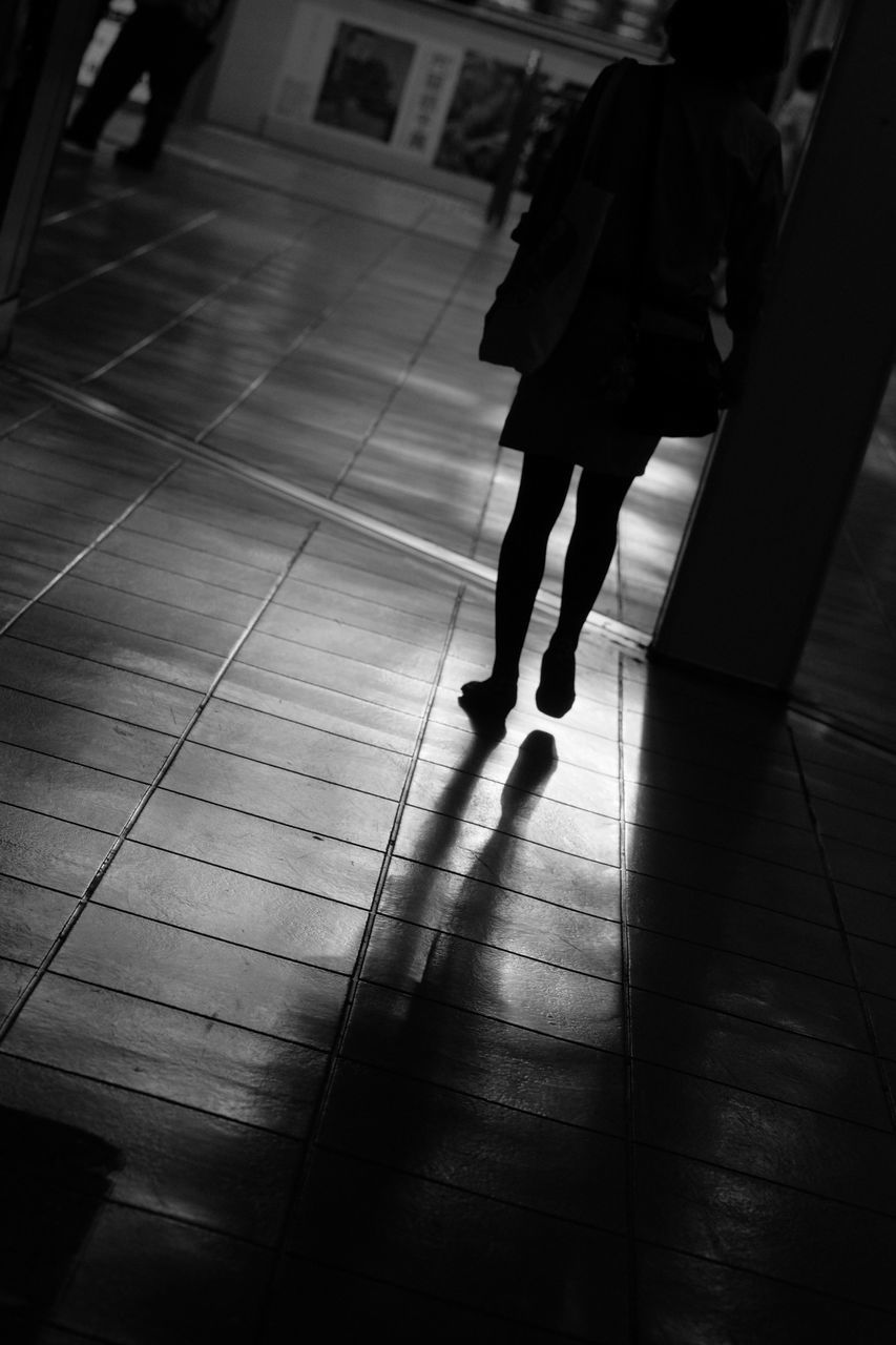 Silhouette Woman Walking On Tiled Floor