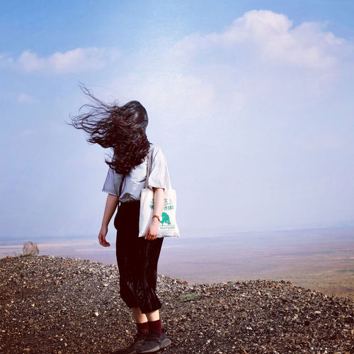 Full length of woman with tousled hair standing on land against sky