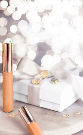 Close-up of beauty products with gift on table