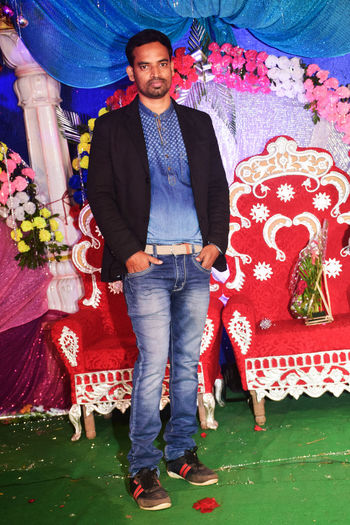 Man in black blazer and blue jeans standing Looking At Camera Real People One Person Front View Portrait Full Length Young Men Leisure Activity Standing Young Adult Flower Casual Clothing Smiling Lifestyles Flowering Plant Red Indoors  Men