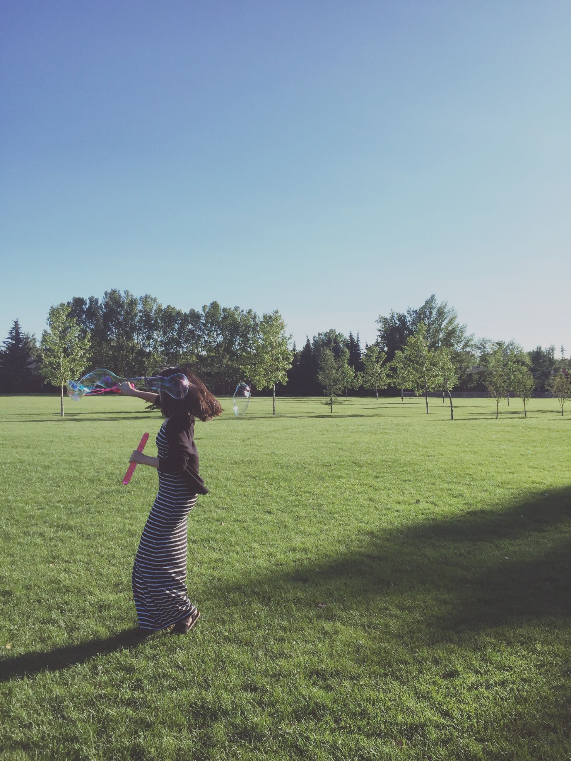 leisure activity, tree, lifestyles, grass, clear sky, field, full length, childhood, copy space, shadow, sunlight, green color, side view, casual clothing, playing, sport, rural scene, innocence, growth, enjoyment, grassy, fun, carefree, day, blue, tranquility, tranquil scene, nature