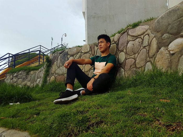 Low angle view of young man sitting on field against wall