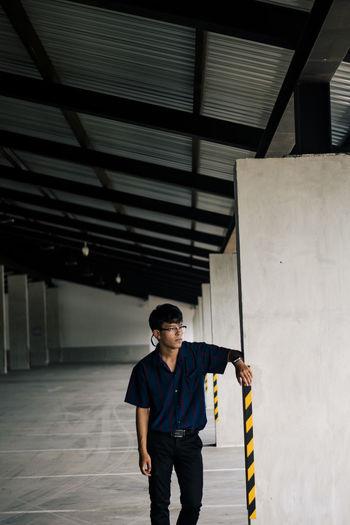 Young man standing in building corridor