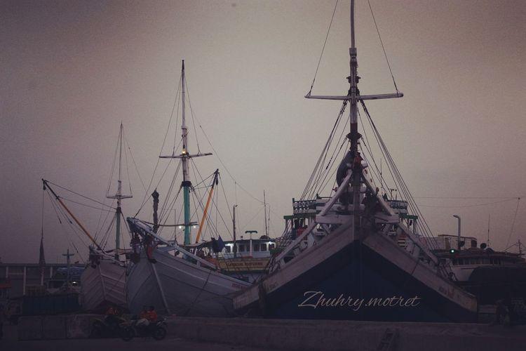 Sailboats moored at harbor against sky
