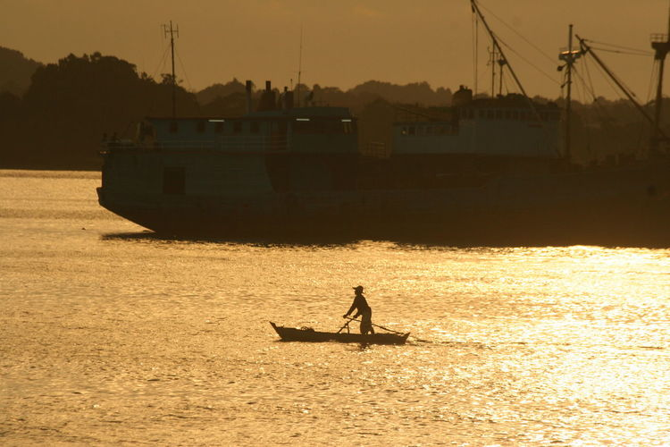 Silhouette man rowing boat against ship during sunset