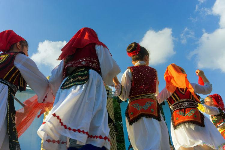Rear view of people dancing against sky