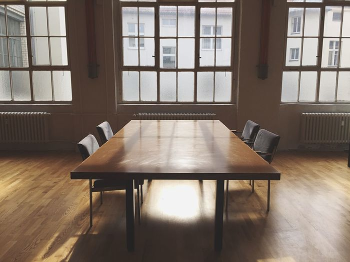 Empty Table And Chairs On Hardwood Floor In Meeting Room