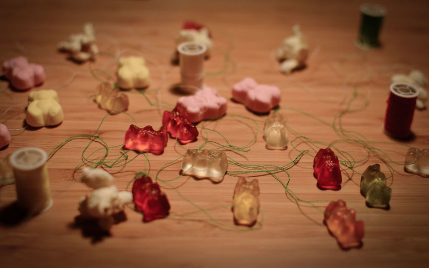 Close-up of gummy bears and strings on table during christmas