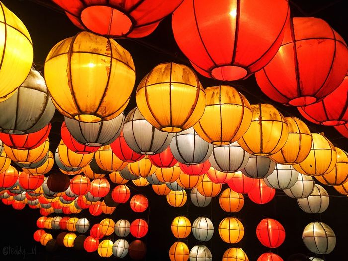 Low angle view of illuminated lanterns hanging against sky at night