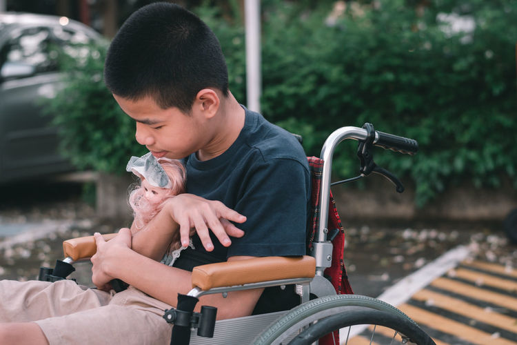 Boy holding doll sitting on wheelchair