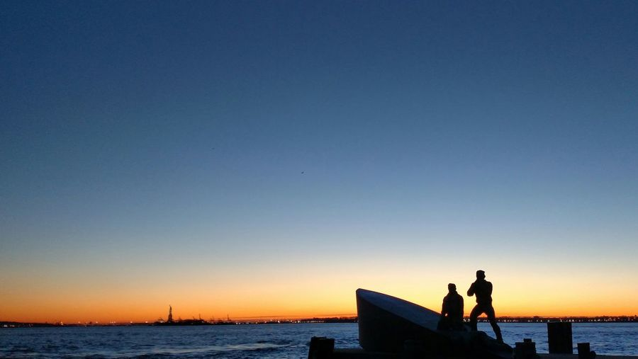 Statues at sea shore against clear sky during sunset