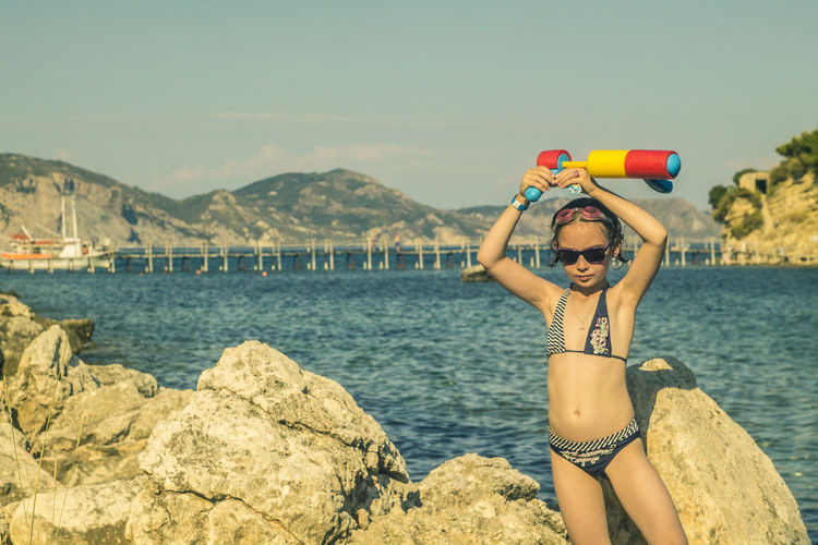 Girl Wearing Bikini At Sea By Rocks Against Sky