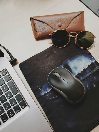 High angle view of sunglasses and laptop on table