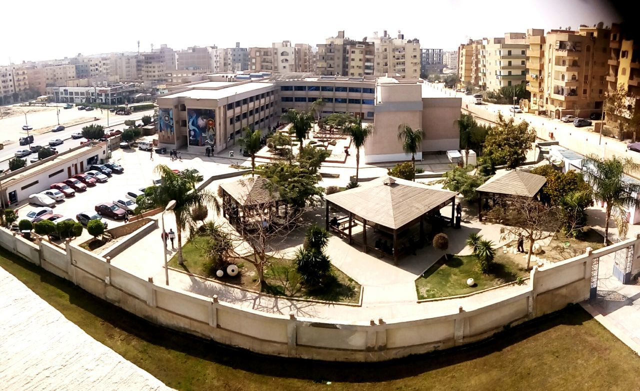 architecture, built structure, building exterior, high angle view, outdoors, sunlight, day, city, tree, no people, clear sky, swimming pool, cityscape, water