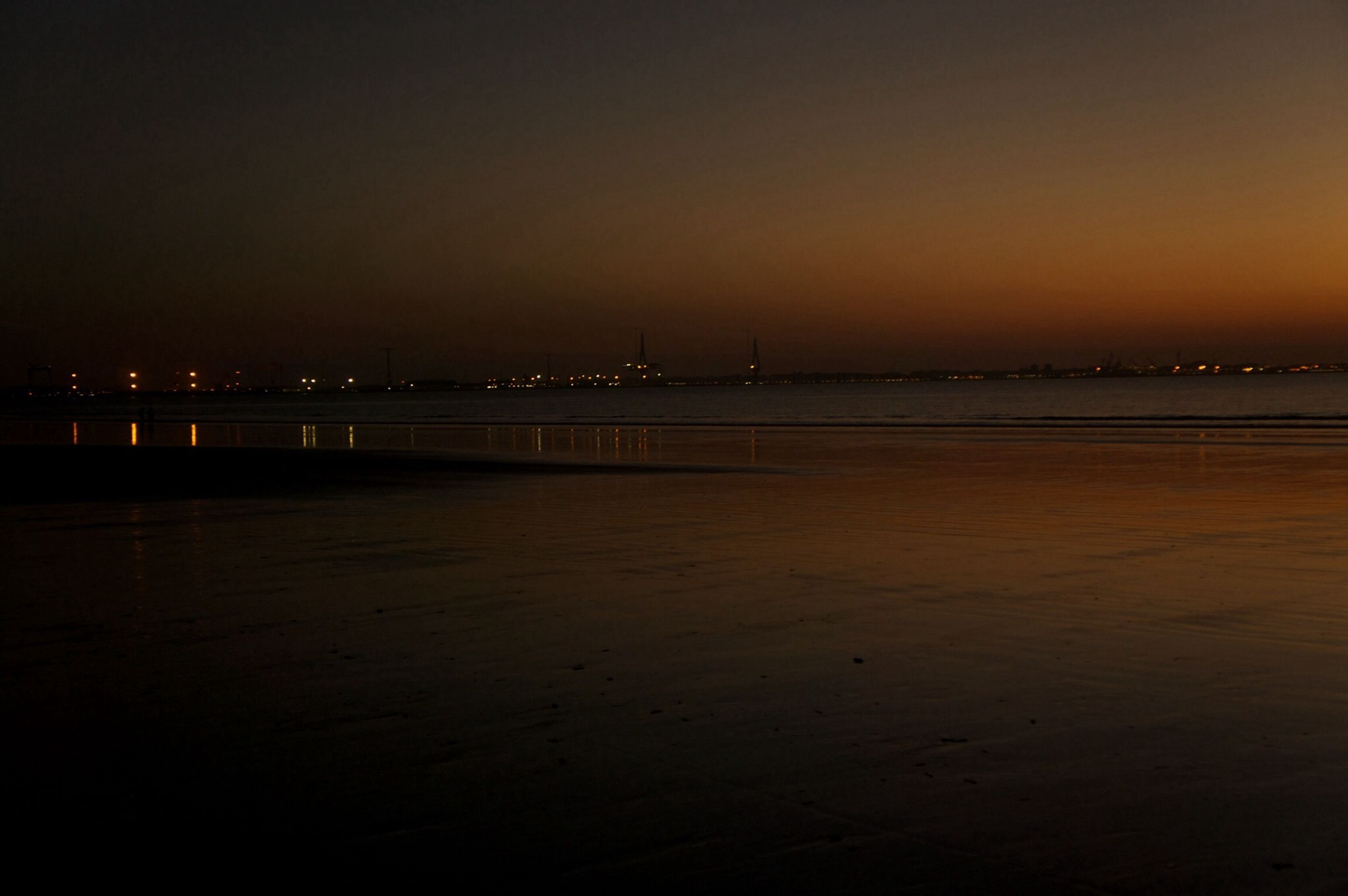 sunset, water, illuminated, silhouette, built structure, copy space, sea, architecture, orange color, beach, dusk, tranquility, night, tranquil scene, scenics, clear sky, bridge - man made structure, connection, sky, nature
