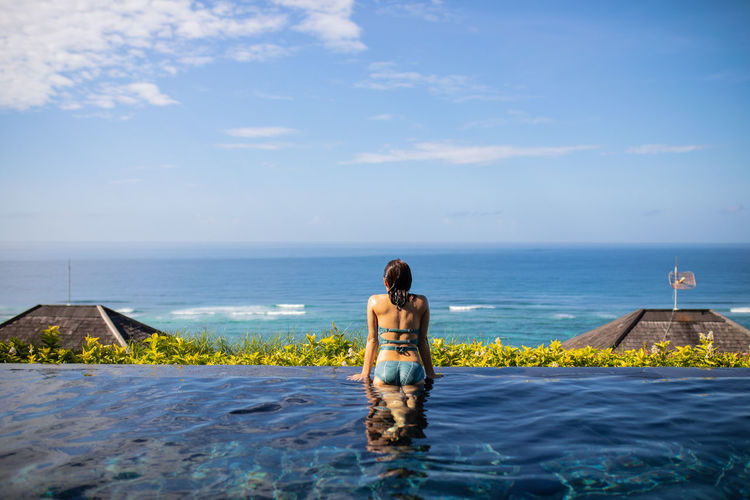 Rear view of woman standing in infinity pool against blue sky