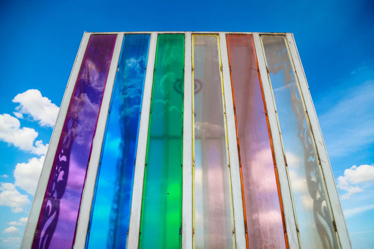 Low angle view of multi colored glass wall against blue sky