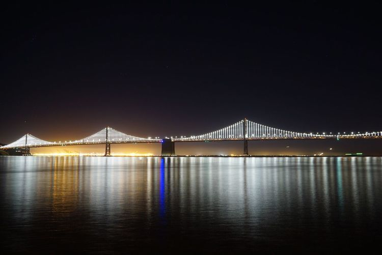 Illuminated Oakland Bay Bridge Over San Francisco Bay Against Clear Sky At Night