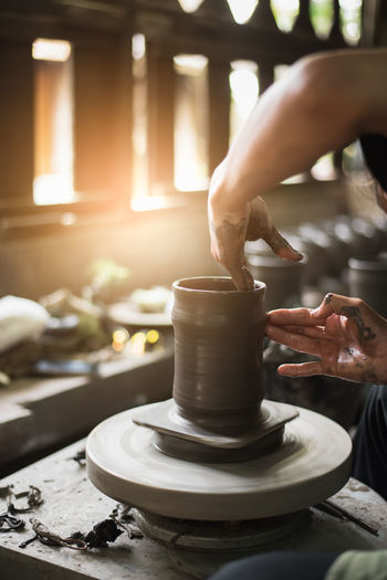Midsection of woman making pottery in workshop