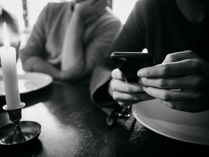 Close-up of man using smart phone while sitting with friend at table