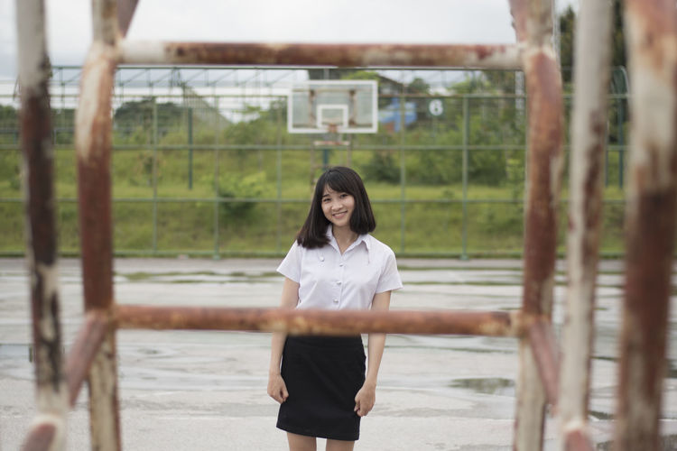 Portrait of smiling young woman seen through metallic outdoor play equipment during rainy season