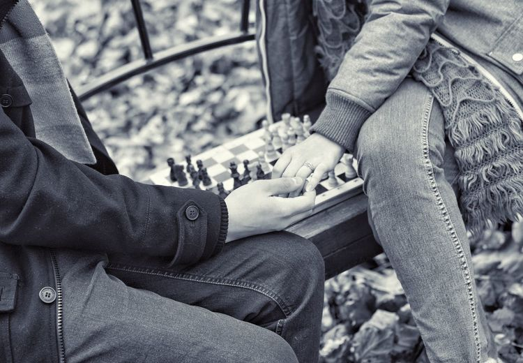 Midsection of couple playing cheese while sitting on bench