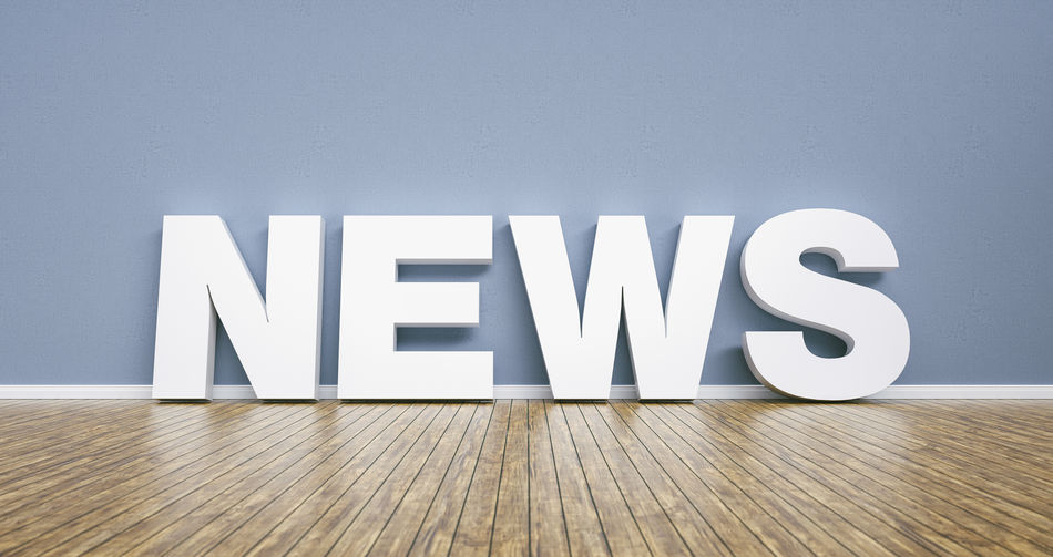 Close-Up Of News On Hardwood Floor Against Wall