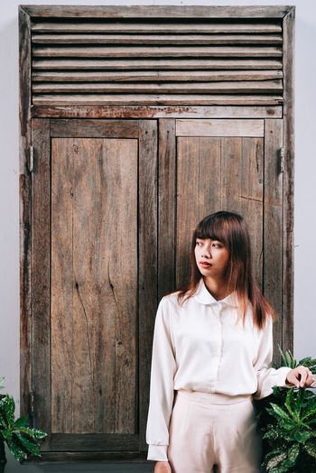 Portrait of woman standing against closed door