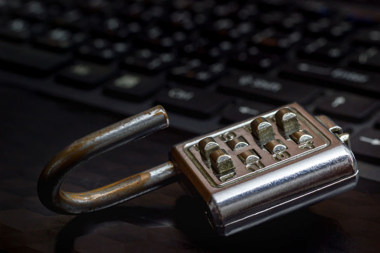 Close-up of metallic padlock by computer keyboard on table
