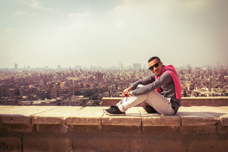 Arab young guy teenager sitting on high wall above the city wearing sunglasses City One Person Sky Cityscape Young Adult Full Length Young Men Sitting Leisure Activity Retaining Wall Wall Casual Clothing Nature Glasses Lifestyles Outdoors Fashion Contemplation Sunglasses Eyewear Arab Man Teenager Aerial View Portrait Above Moments Of Happiness