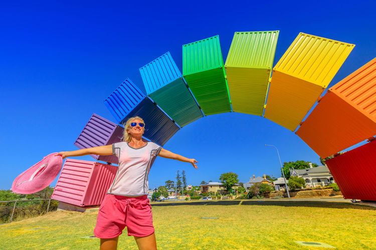 Happy woman with open arms looking Rainbow Sea Container in Fremantle, Western Australia. Female tourist enjoys at Fremantle welcome. Homosexuality and hope concept Freemantle Perth Perth Australia Western Australia Australia Australian Rainbow Bridge Colorful Rainbow Colors Rainbow🌈 Blue Sky Woman Homosexual Love Pink Color Girl Females Happy Happyness Sky One Person Leisure Activity Nature Lifestyles Real People Multi Colored Women Day Casual Clothing Front View Standing Young Adult Portrait Fun Blue Full Length Grass Enjoyment Outdoors