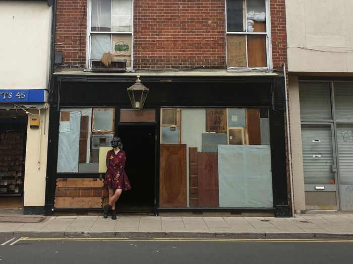 Woman walking on footpath by building