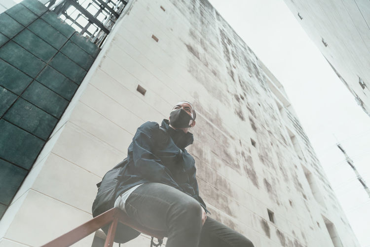 Low angle view of man wearing mask sitting against building