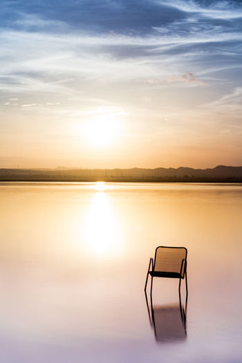 Chair on lake against sky during sunset