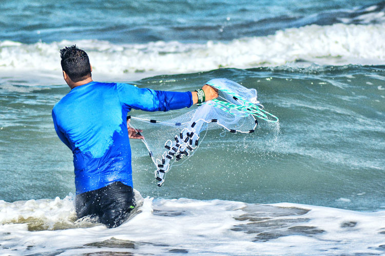 Rear view of man surfing in sea