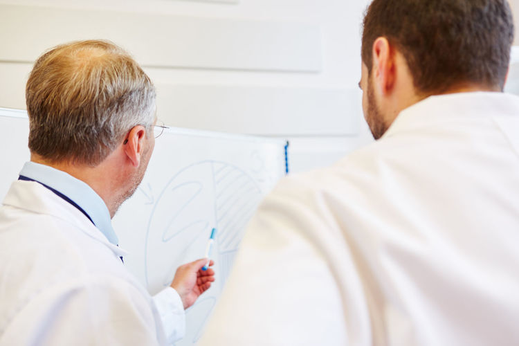 Rear View Of Senior Doctor Giving Presentation To Colleague In Hospital