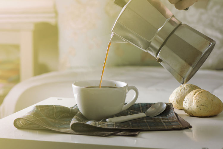 Woman serving hot coffee in the living room of his home in the morning Breakfast Coffee Cupcakes Hot Morning Served Steaming Woman Bread Coffeepot Cup Dirnk Drink Filtered Hand Handle Maker Making Pour Serving