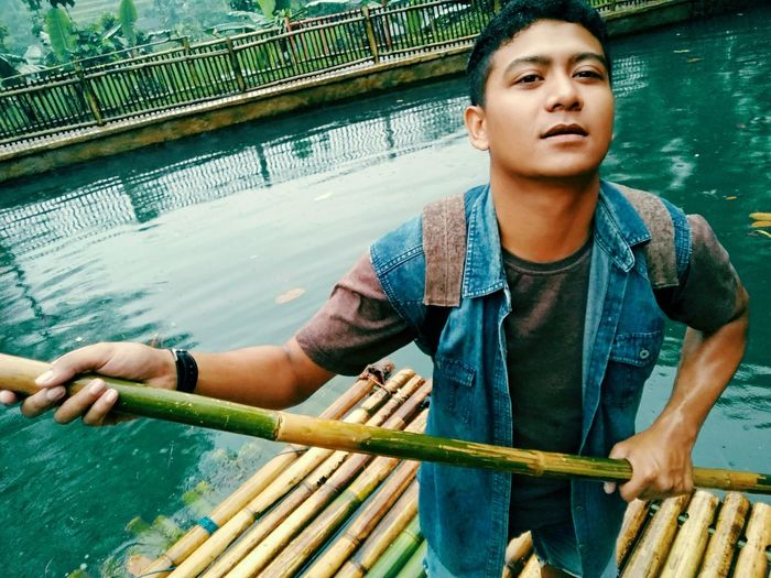 Portrait of young man standing on wooden raft