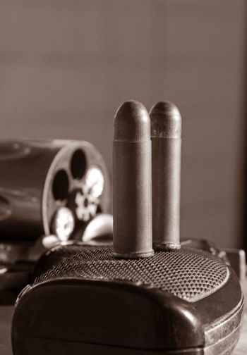 Close-Up Of Gun With Bullet On Table