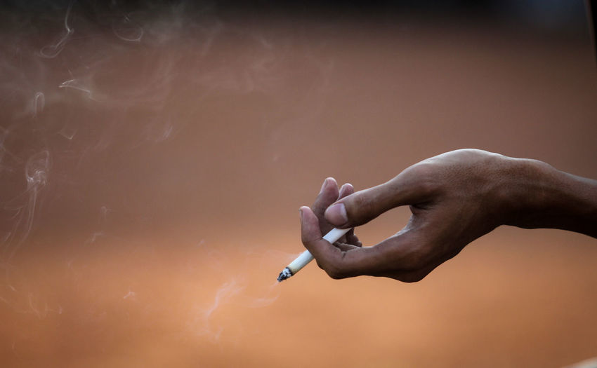 Close-up of a hand holding cigarette Close Up Bad Habit Smoking Cigarette  Fresh On Market 2018