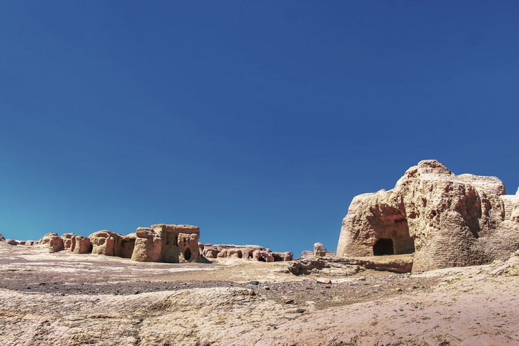 Panoramic view of rock formations against clear blue sky