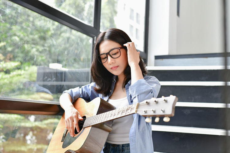 Young woman holding guitar on staircase by glass window