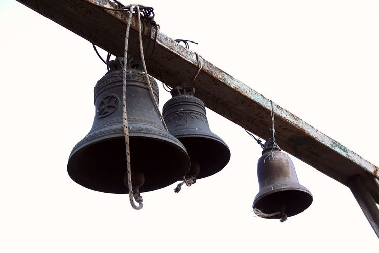 Low angle view of bell hanging against clear sky