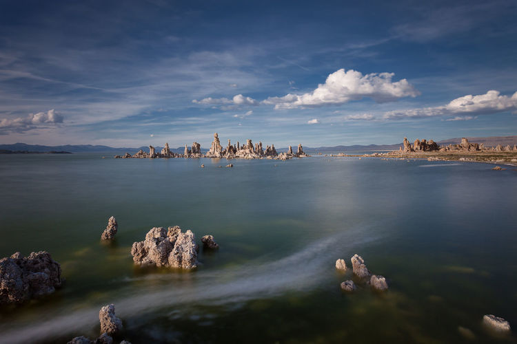 Idyllic shot of rock formations in mono lake against sky