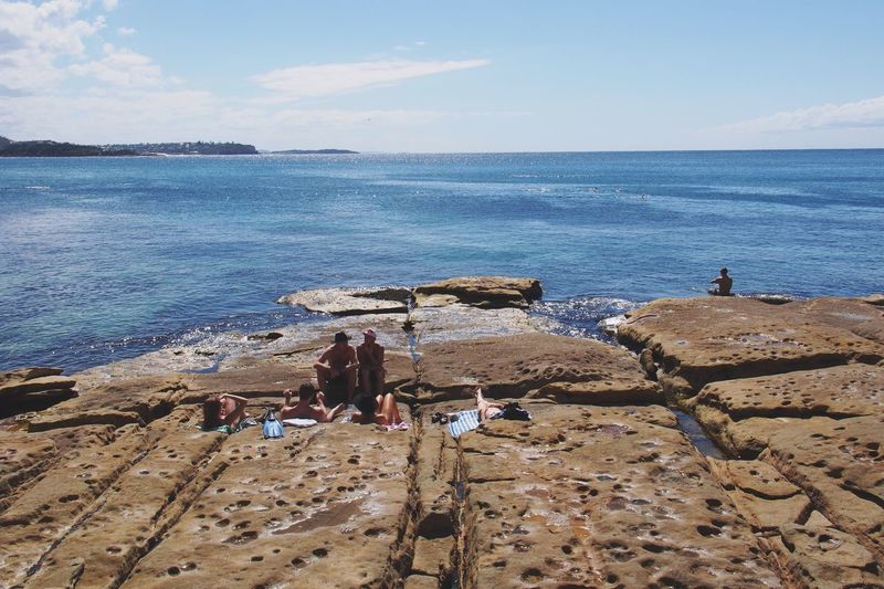 Idyllic View Of Sea With People Sunbathing On Rocks At Manly Beach