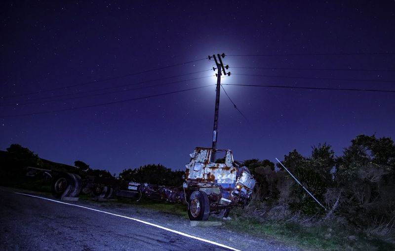 Cable Connection Electricity  Electricity Pylon Field Illuminated Land Land Vehicle Men Mode Of Transportation Motor Vehicle Nature Night Outdoors Power Line  Road Sky Technology Transportation Tree Two People